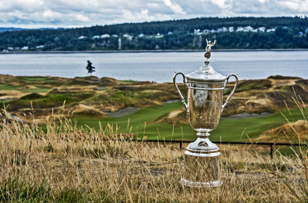 US Open trophy on grassy field against golf course backdrop