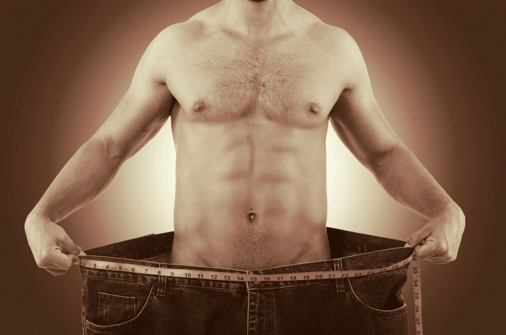 muscular man in oversized jeans holding them out to illustrate weight loss concept