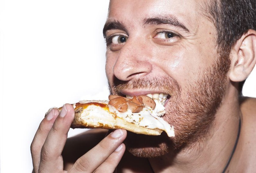 Close-Up Of A Man Eating A Slice Of Pizza with mozzarella and sausages