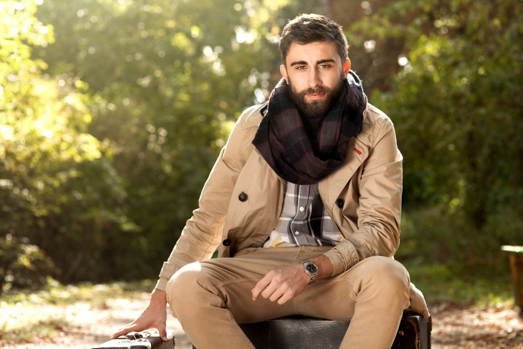 Fashion photo of young handsome man with suitcases in park. Autumn. Men wearing coat and scarf. Sunny day.