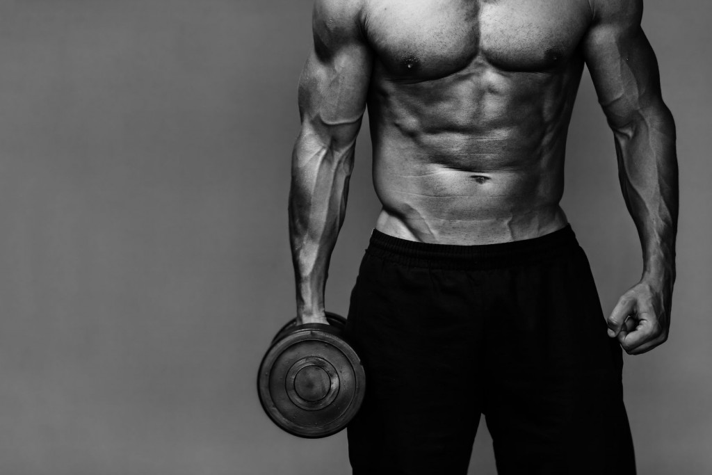 Close up of muscular bodybuilder guy doing exercises with weights over grey background - Black and white