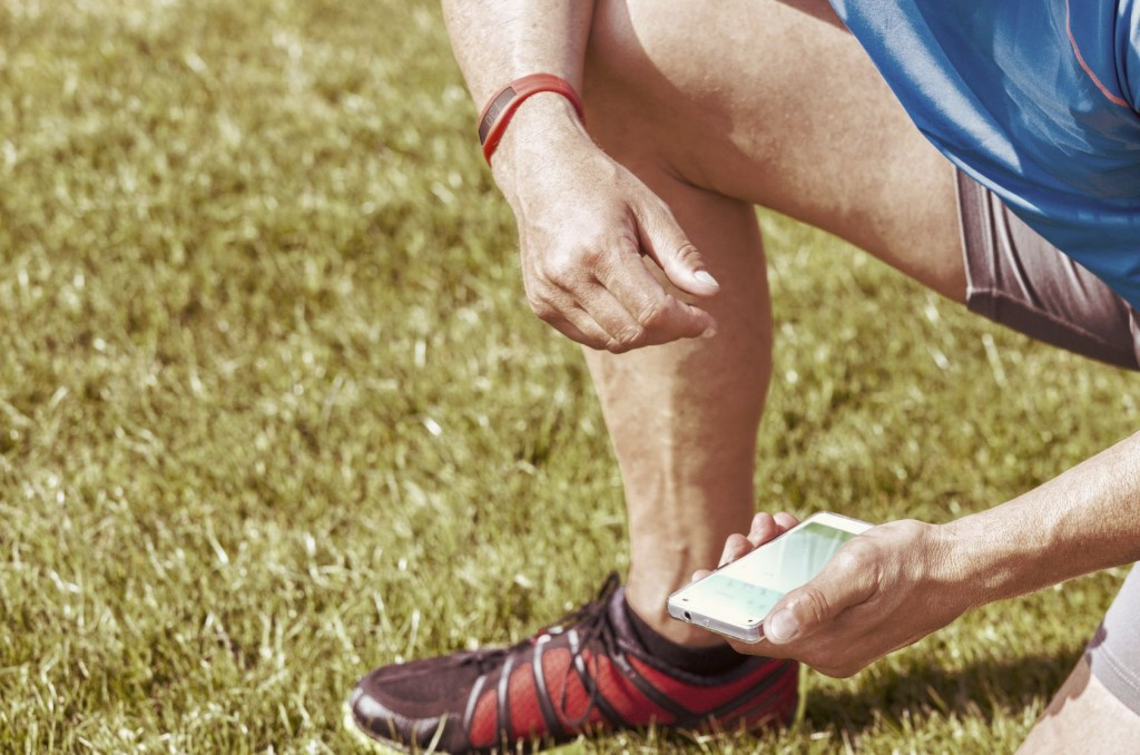 Sportive man kneels on a lawn and checks his fitness results on a smartphone