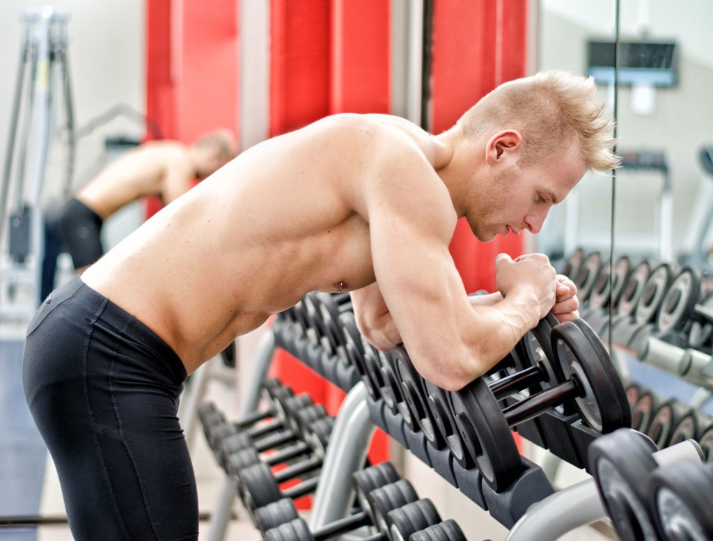 athletic man resting on dumbbells rack after workout in gym