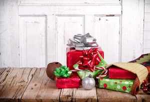 Christmas presents spilling out of a stocking on wooden plank with antique door panel background