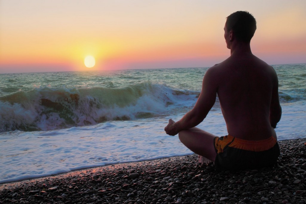 Man meditating on the shore of the sea