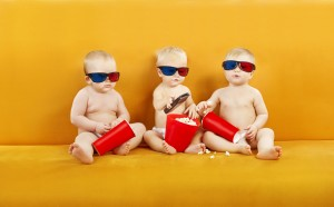 three babies wearing 3d glasses and holding popcorn buckets
