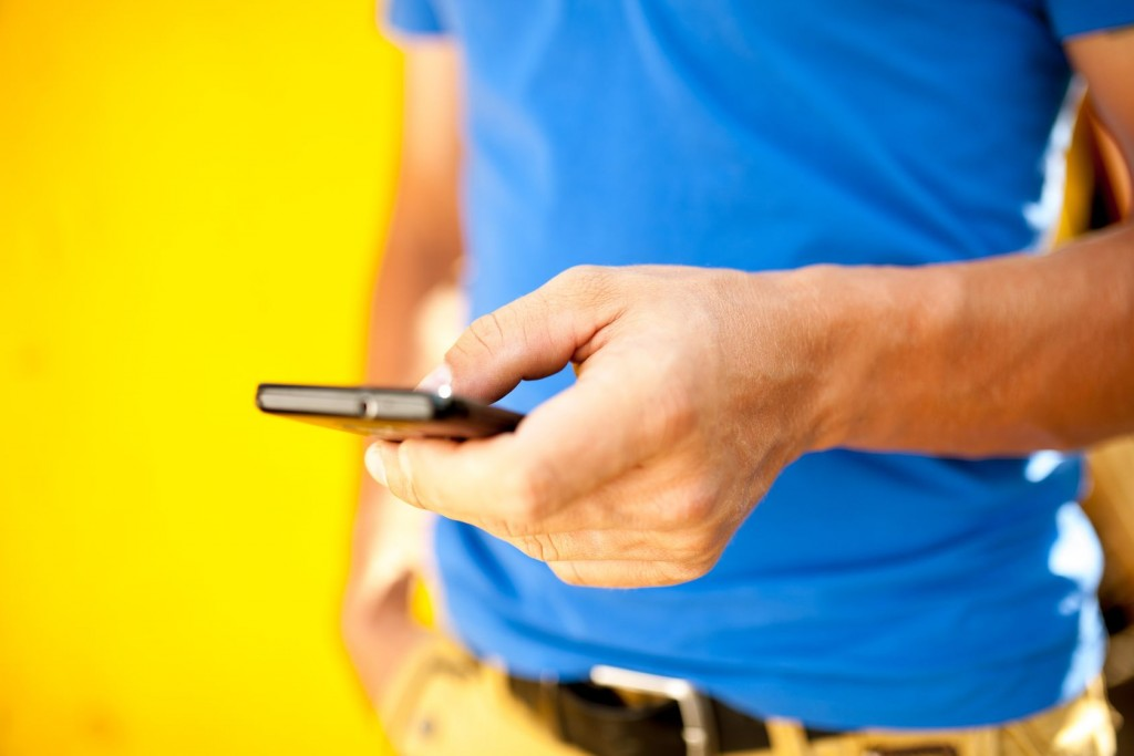 man with phone on yellow background