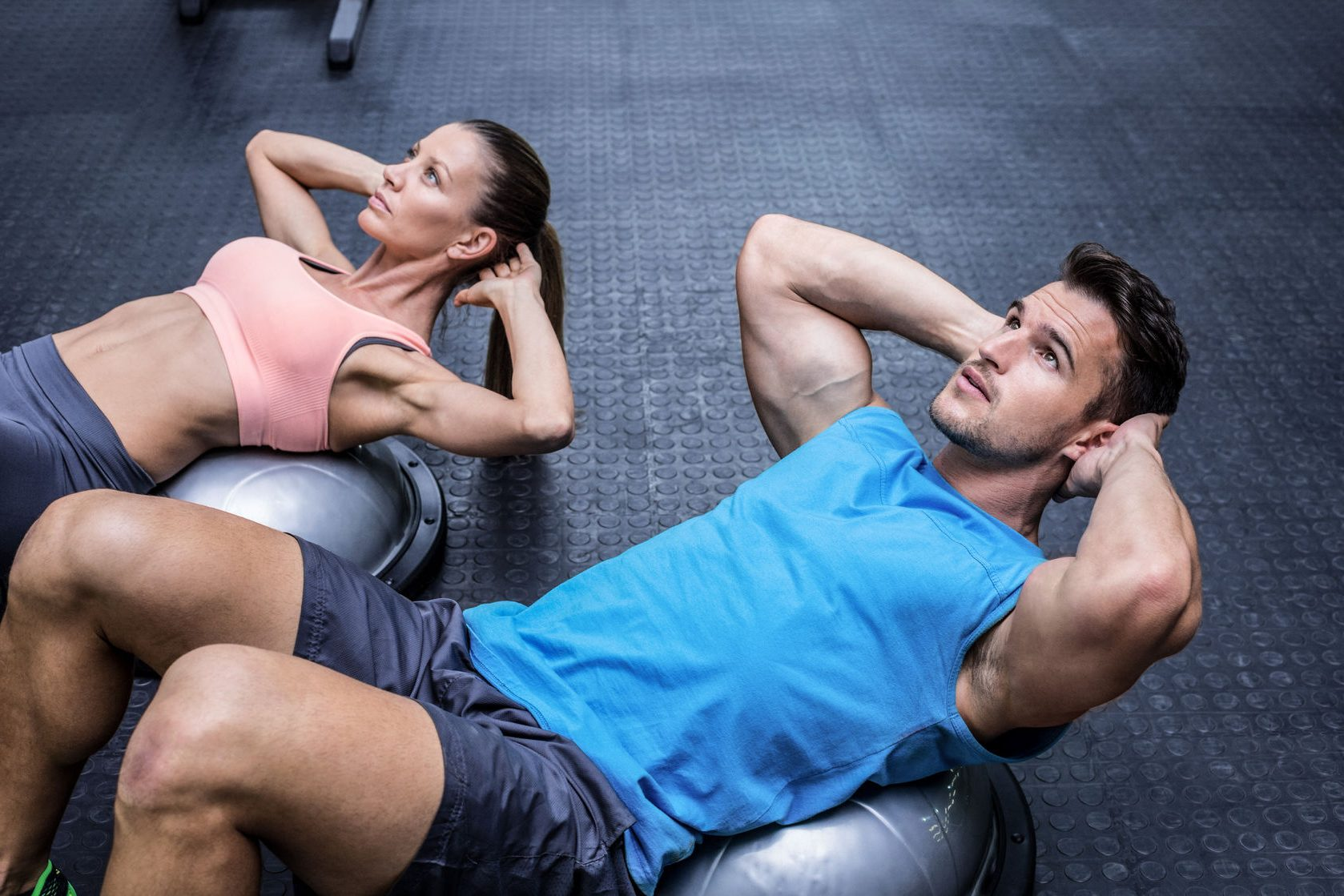 42329473 - muscular couple doing abdominal crunch on a bosu ball
